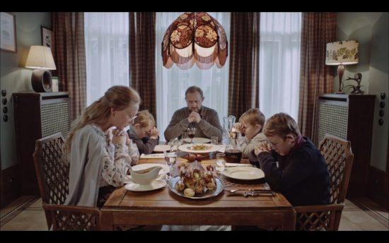 Cate Blanchett bendiciendo la mesa familiar con el manifiesto de Claes Oldenburg, en Manifest, Julian Rosefeldt, 2015